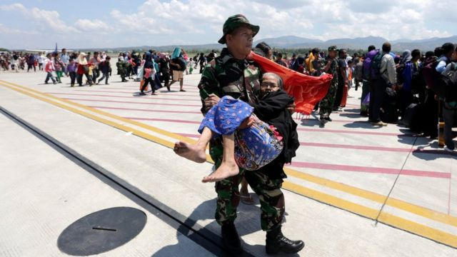 An Indonesian soldier carries an elderly woman evacuated after an earthquake and tsunami at Mutiara Sis Al Jufri airport in Palu, Central Sulawesi, Indonesia, October 1, 2018 in this photo taken by Antara Foto