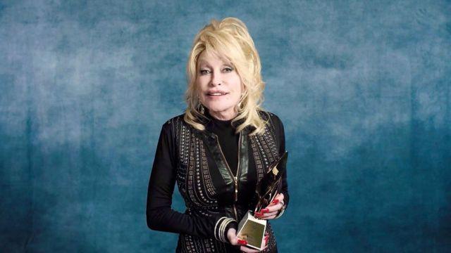 Dolly Parton with a Billboard Award.