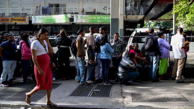 Una fila de gente para comprar bienes básicos.