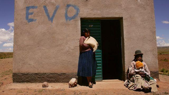 Dos mujeres frente a una vivienda