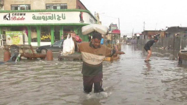 Man wading through water in Baghdad