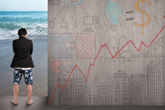 Hombre vestido de ejecutivo arriba y traje de baño abajo mirando a la playa al lado de un muro con cuestiones comerciales.
