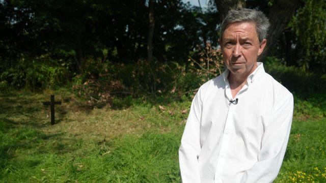 Detetive aposentado Nick Chalmers diante do túmulo não identificado do menino em Londres