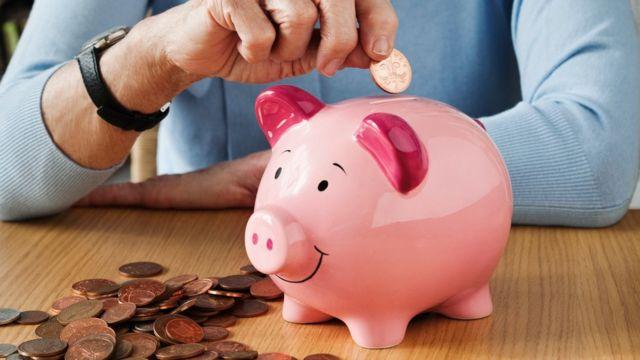 Mãos colocam moedas em um cofre em formato de porquinho
