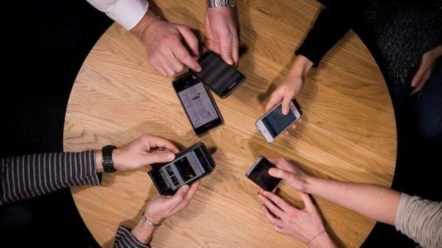 모여 앉아 휴대폰을 보고 있는 사람들