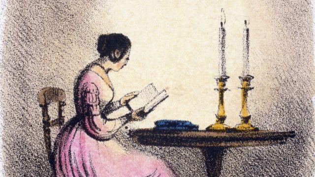 Mujer leyendo a la luz de las velas