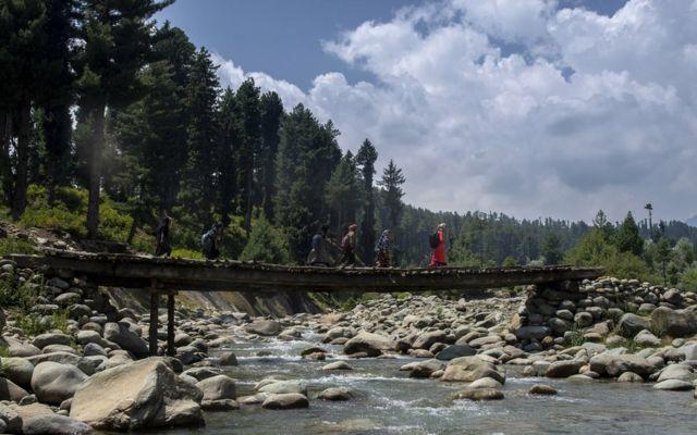 Students walking to school on a bridge in Kashmir.