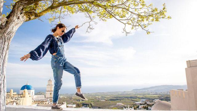 Chica balanceándose sobre muro
