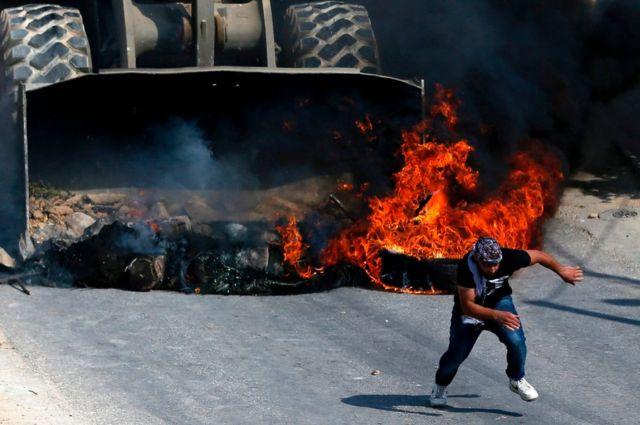 Manifestante palestino huye de un tractor de Israel.