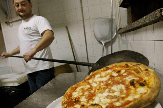 Cocinero sacando pizza