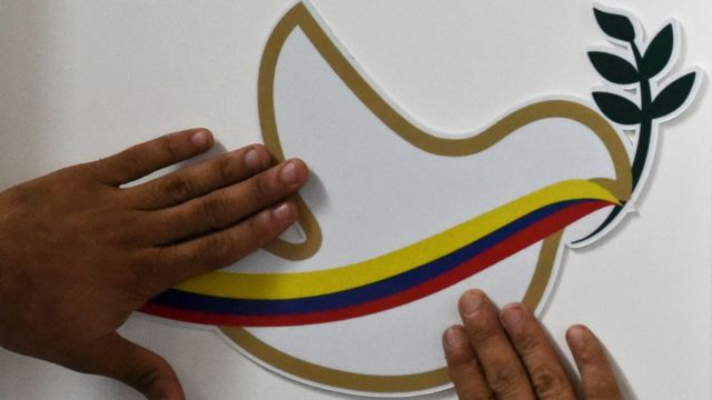 Un hombre intenta ajustar sobre una pared una cartulina con una paloma de la paz y la bandera de Colombia.