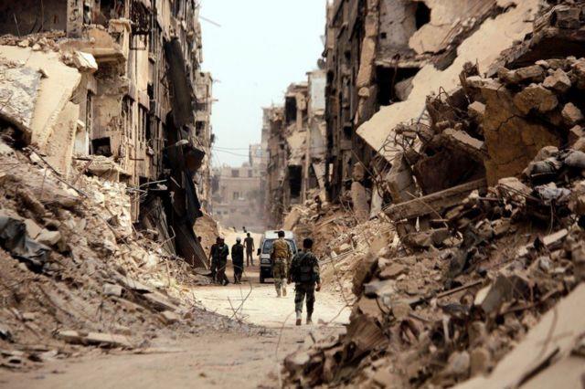 Para tentara berjalan melewati bangunan yang hancur di kamp Yarmouk Palestina di Damaskus, Suriah.