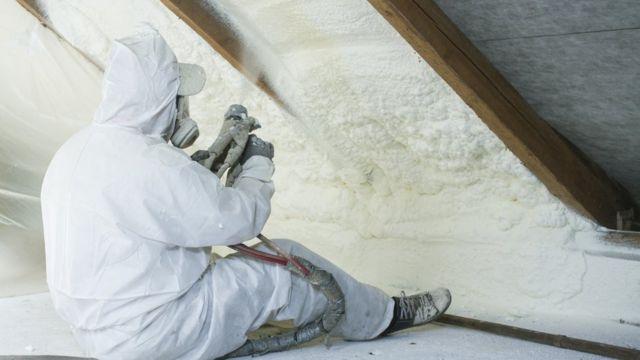 A technician sprays polyurethane foam used as roof insulation (stock photo)
