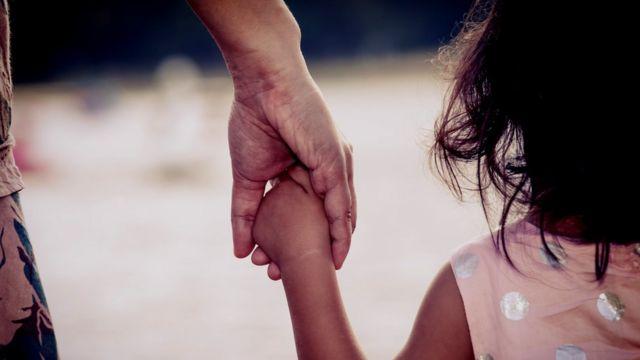 मां का हाथ पकड़े बच्ची