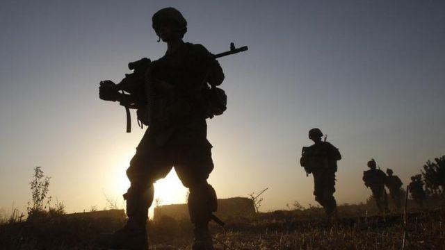 Soldados americanos caminhando em terreno aberto e aparecendo a contraluz