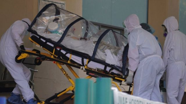 Paciente isolado por capa plástica é levado em maca acompanhado por profissionais de saúde que usam equipamentos de proteção
