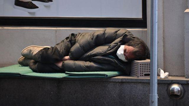 Homem sem-teto dorme na calçada da cidade de Daegu