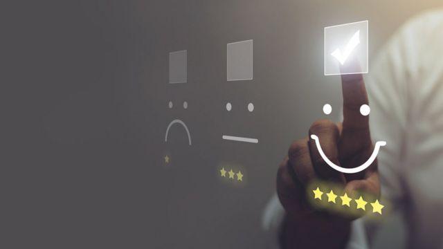 Em painel com projeção de três carinhas - uma indicando um rosto feliz, uma mais ou menos e outra triste -, dedo aponta para a carinha feliz