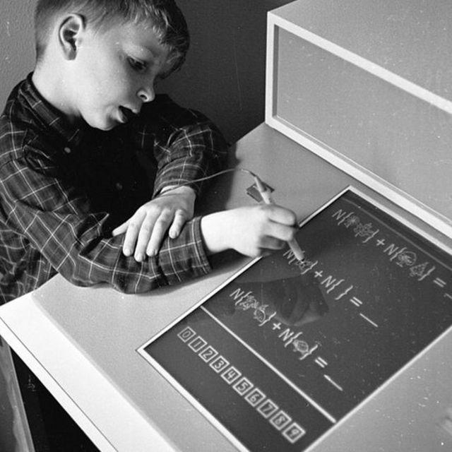 Un niño aprendiendo matemáticas en una pantalla táctil in 1965