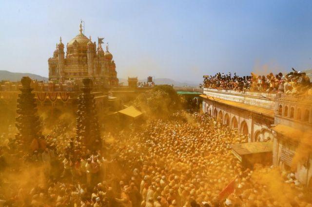 Паломники развеивают куркуму в дар индуистскому божеству Кхандобе в праздник новолуния в деревне Джедзури, Индия.