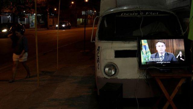 Pronunciamento de Bolsonaro é exibido em TV no meio da rua à noite no Rio de Janeiro, ao lado de combe e pedestre