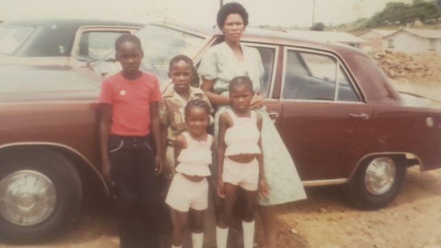 Agnes Sithole e seus quatro filhos em frente a um carro vermelho