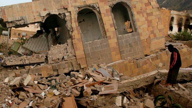 رجل يقف وسط حطام منزل دمر خلال مواجهات في مدينة تعز عقب إعلان الهدنة