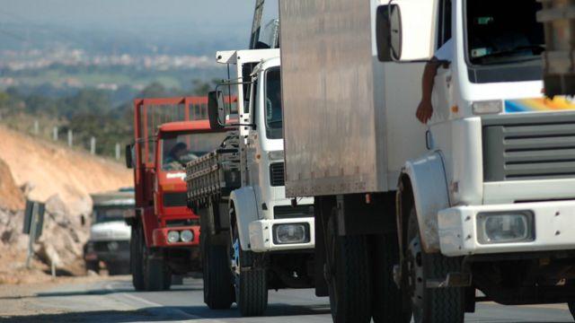 Sequência de quatro caminhões circulando em estrada