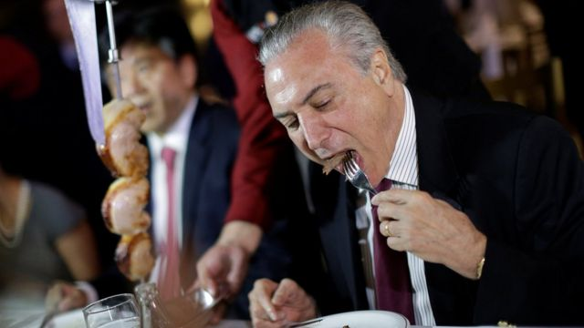 Brazil's President Michel Temer eats barbecue in a steak house after a meeting with ambassadors of meat importing countries of Brazil, in Brasilia, Brazil March 19, 2017.