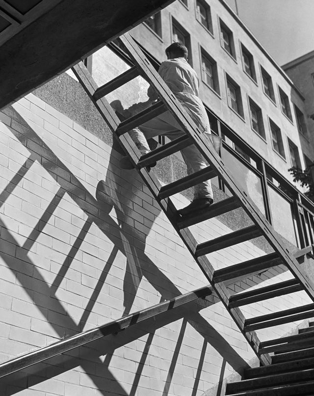 Мойщик окон балансирует на лестнице. Берлин, середина 1930-х годов