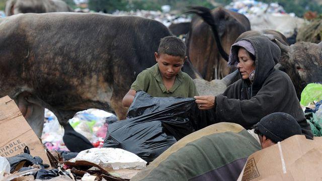 Una mujer y su hijo buscan comida entre la basura.
