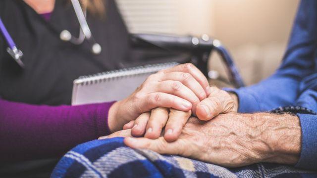 Doctora agarrando las manos de una paciente mayor