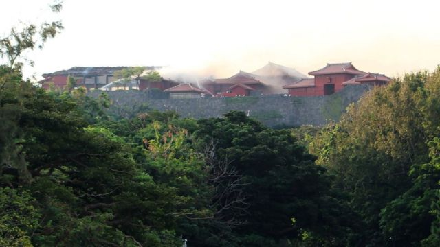 Firefighters spray water on the Shuri Castle in Naha
