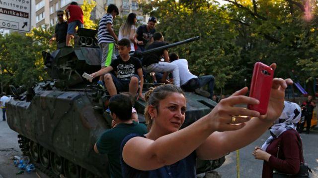 損傷した戦車の前で写真を撮る女性(16日、アンカラ市内)