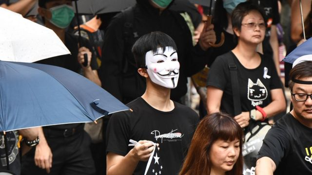 A protester (C), seen wearing a Guy Fawkes mask and holding a representation of the Chinese national flag coloured black,