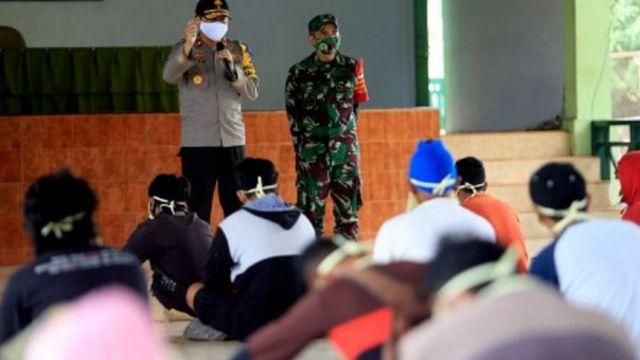 """""""Pihak gugus tugas sudah melakukan berbagai cara misalnya merayu tapi masih belum (mau diisolasi) juga.  """"Kita bukan maksud mengepung, tapi memberi saran bahwa kita harus mendata kluster mana covid-19 yang menyebar. Sebab di Aceh Barat belum ada kasus,"""" ujar Amril Nuthihar kepada BBC lewat sambungan telepon, Senin (10/08).  Setelah empat jam terjadi perdebatan, pihak keluarga akhirnya bersedia diisolasi.  Amril menjelaskan keterlibatan TNI dalam penanganan penyebaran covid-19 sudah termuat dalam Surat Keputusan Percepatan Penanganan Virus Corona.  Dalam struktur Gugus Tugas penanganan pandemi itu, bupati sebagai ketua dan Komandan Distrik Militer atau Dandim sebagai wakilnya.  Salah satu kegiatan bersama tentara di kabupatennya, kata Amril, berpatroli ke area perbelanjaan bersama petugas kecamatan. Ia mengklaim, dengan mengajak tentara warga menjadi lebih patuh pada protokol kesehatan.  """"Orang kalau lihat pakai baju loreng pasti mau (patuh), tapi kalau pakai baju biasa pasti tidak mau dengar,"""" tukasnya.  Mengapa pelibatan TNI dipertanyakan pakar kesehatan? Hanya saja pelibatan tentara seperti yang terjadi di Kabupaten Aceh Barat disesalkan Pakar Epidemiologi dari Fakultas Kesehatan Masyarakat, Universitas Indonesia, Pandu Riono.  Kata dia, petugas dari gugus tugas semestinya menggandeng pemuka agama atau tokoh masyarakat setempat ketimbang tentara ketika mengalami kendala.  """"Ya tidak perlu dikepung, harus ada pihak-pihak entah itu pemuka masyarakat yang bisa memberitahu dan itu cuma isolasi. Kalau mau isolasi di rumah tidak apa-apa,"""" ujar Pandu Riono kepada BBC News Indonesia, Senin (10/08).  """"Kan mereka bukan penjahat juga,"""" sambung Pandu.  Dia juga menilai pelibatan TNI tidak akan menyelesaikan masalah mengenai kepatuhan masyarakat terhadap protokol kesehatan. Sebab ketidaktahuan publik turut, menurutnya, disumbang oleh sikap pemerintah yang belum mengedukasi masyarakat dengan tepat.  """"Selama pandemi ini kan banyak informasi tidak akurat, baik disampaikan pemerint"""