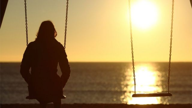 Person sitting on a swing with back to the camera looking into the distance as sun sets in the background