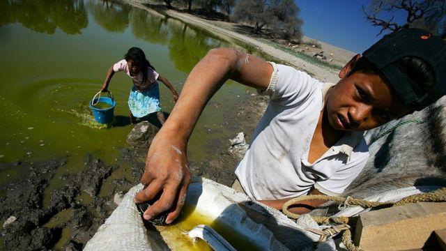 Niños sacando agua de un lago en México.