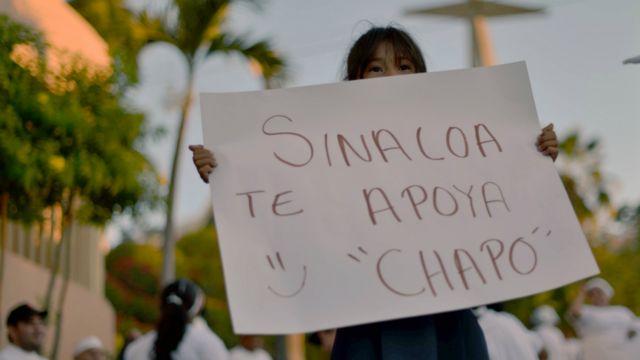 Una niña con un cartel de apoyo al Chapo