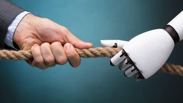 Mano de hombre disputando soga con mano de robot