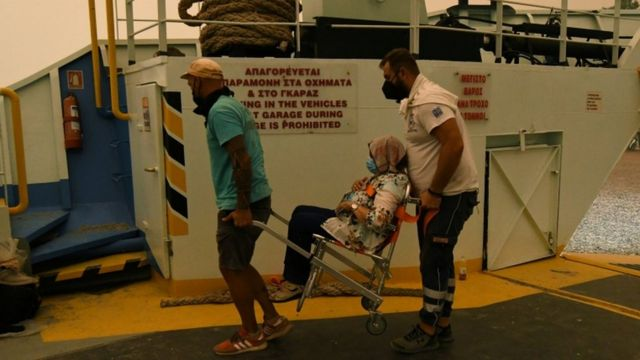 A woman is taken to the ferry in Evia.