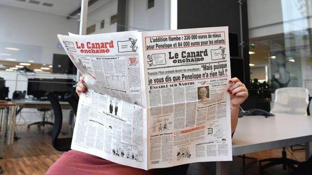 Una lectora de Le Canard Enchaîné sostiene un ejemplar del diario