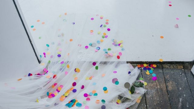 Bride leaves her ceremony with the train of her dress covered in coloured confetti