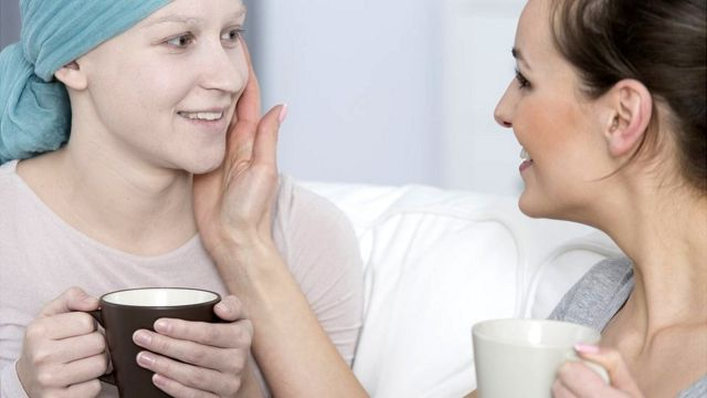 Una mujer con cáncer y una amiga tomando café.