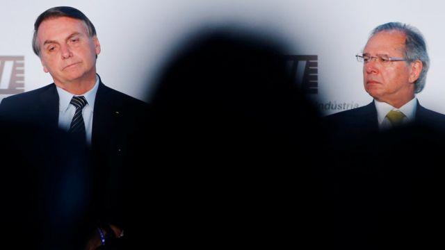 Jair Bolsonaro e Paulo Guedes aparecem sentados em evento, o presidente olhando para baixo e o ministro para o lado