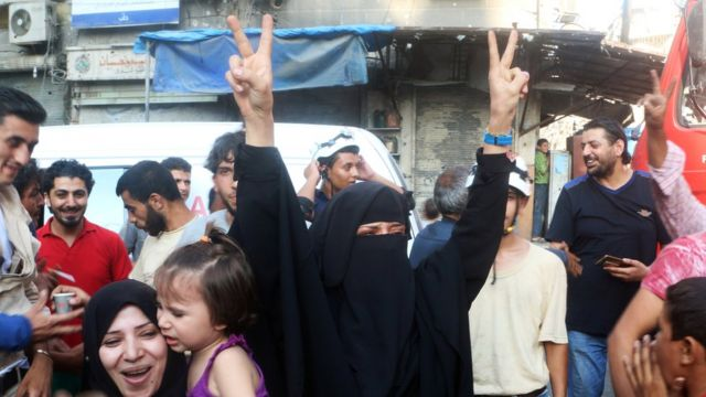 A woman flashes the victory sign as she celebrates the news of the breaking of the siege of rebel-held areas of Aleppo