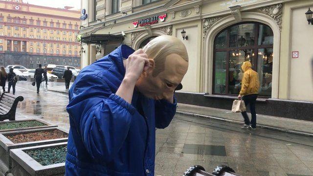 Russian protester Roman Roslovtsev wearing a Vladimir Putin mask