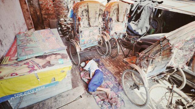 Kishan Lal deitado no chão de um depósito, ao lado de riquixás não usados