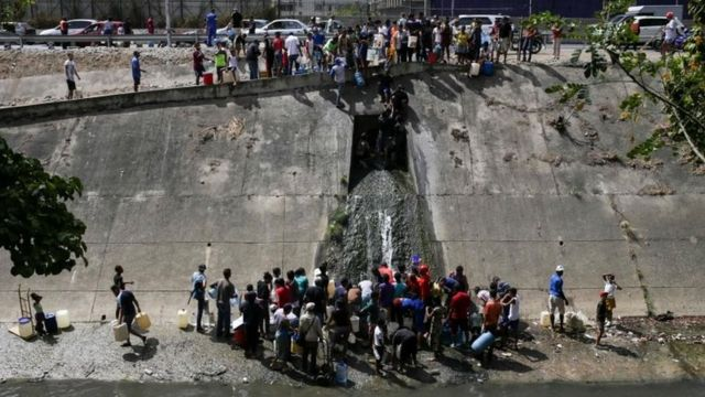 People collect water from a sewage canal at the river Guaire in Caracas on March 11, 2019,