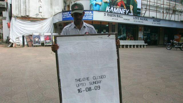 Homem segura cartaz em que diz que o teatro está fechado